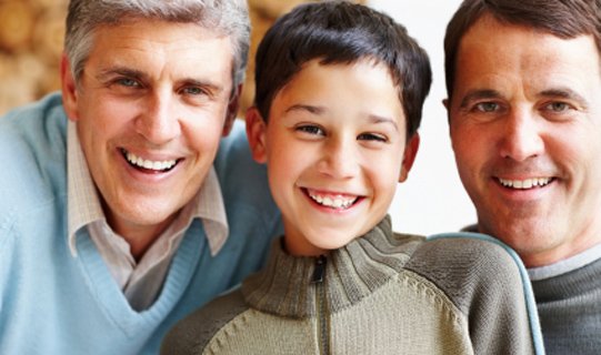Closeup of three generational male family smiling